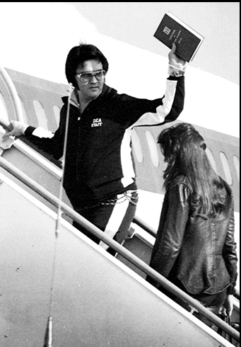 Elvis boarding plane in 1977 holding up book