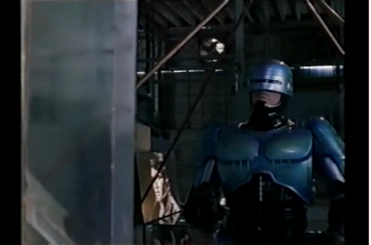 Robocop 2 still frame with Robocop and Elvis photo in same frame